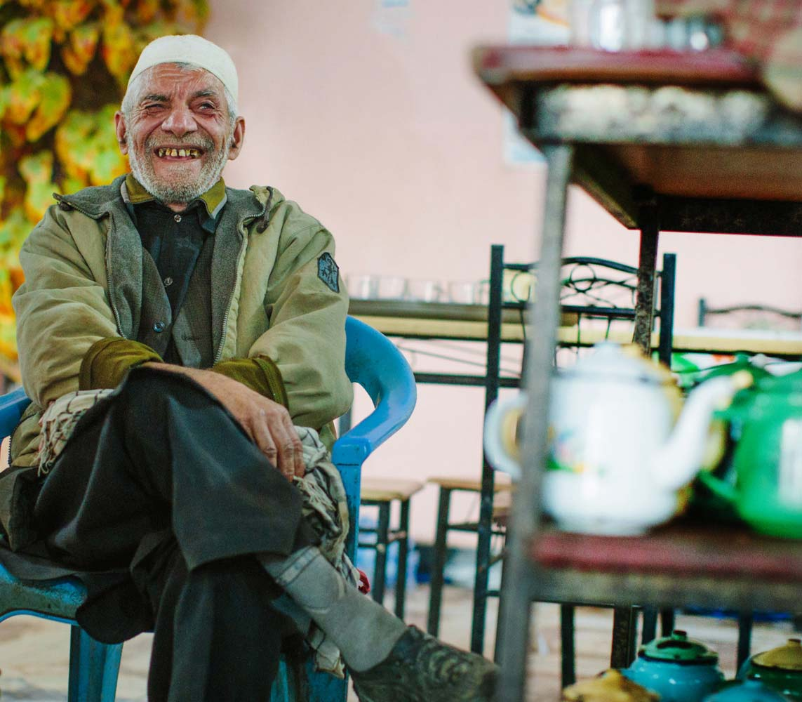 Older gentleman sitting in a chair smiling