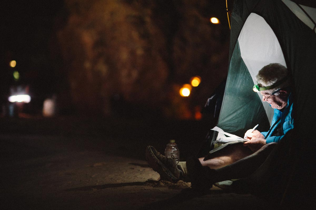 Man writing in a notebook inside of a tent