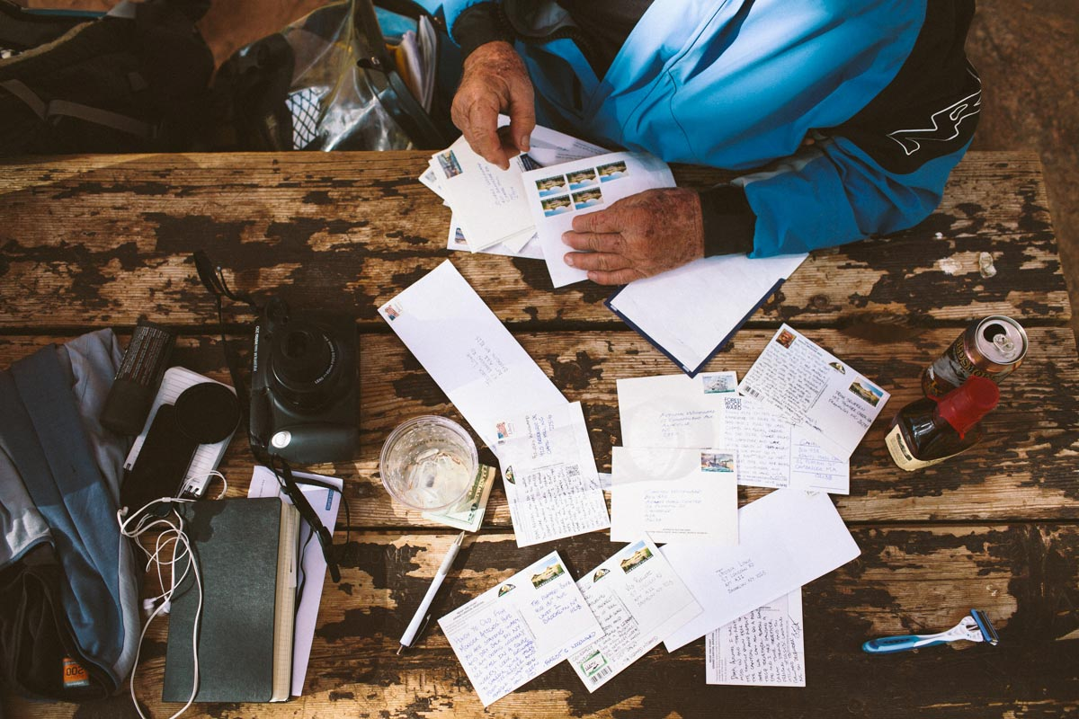 Man sorting through post cards on a wooden table
