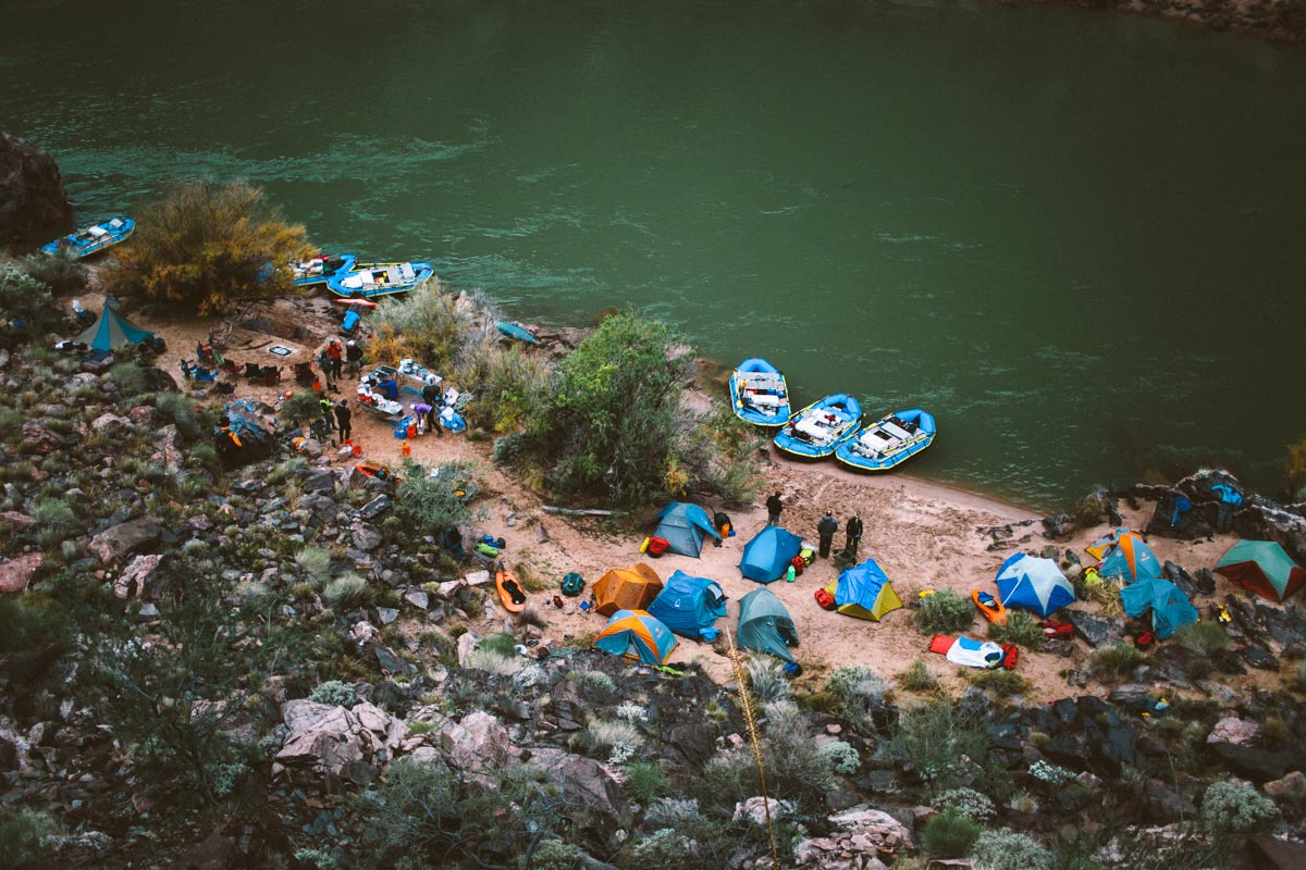 A group of tents and canoes alongside a river shore