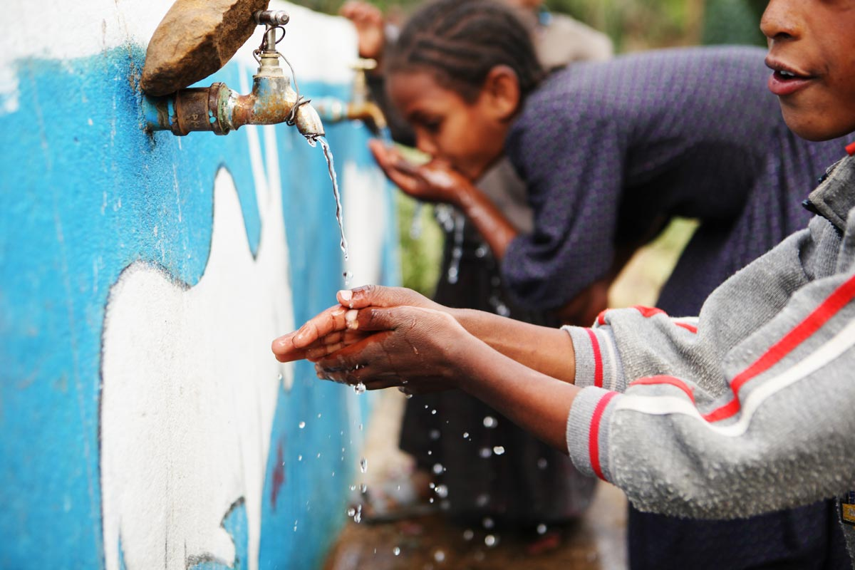 Young children reaching for public drinking water