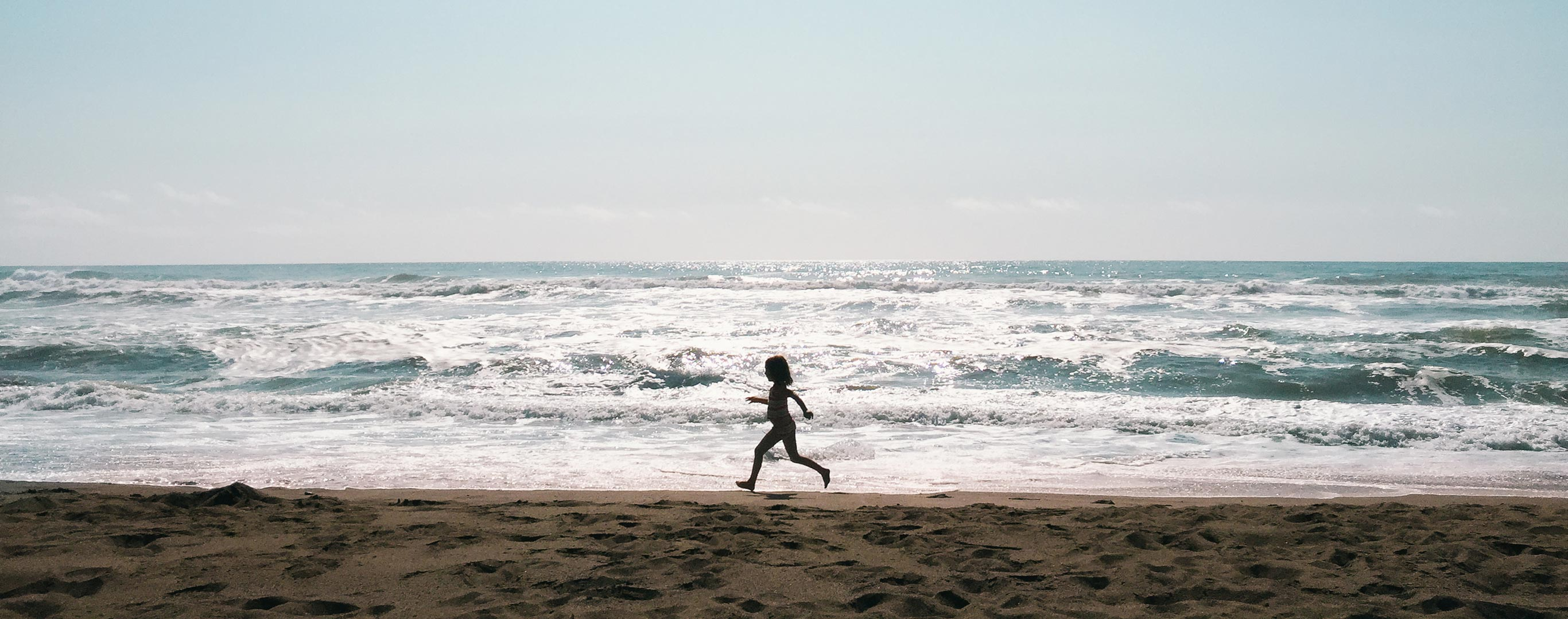 Young child running along the shoreline