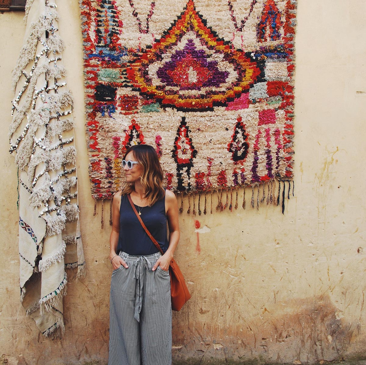 Woman posing next to rug on dirty wall
