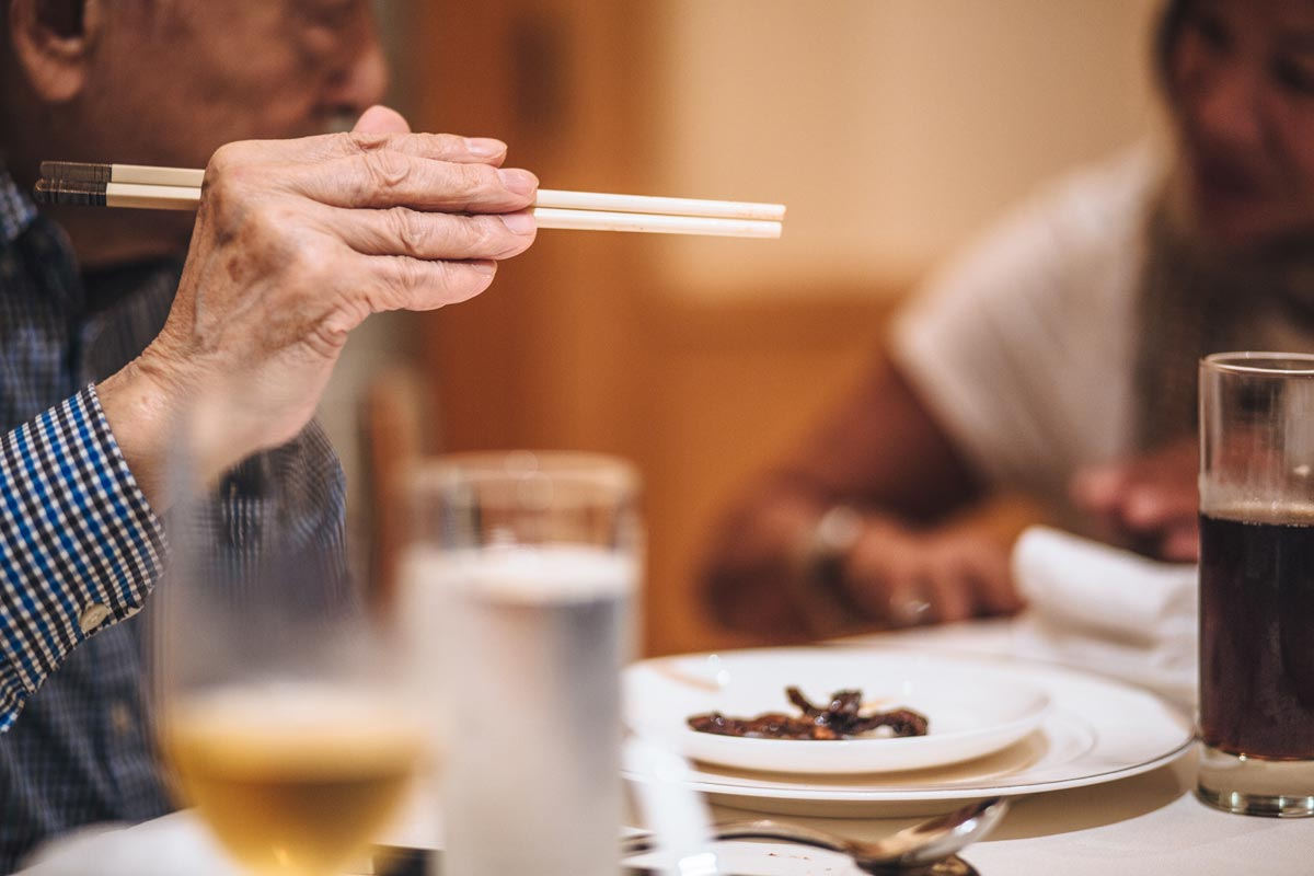 Person holding chopsticks at a dinner table