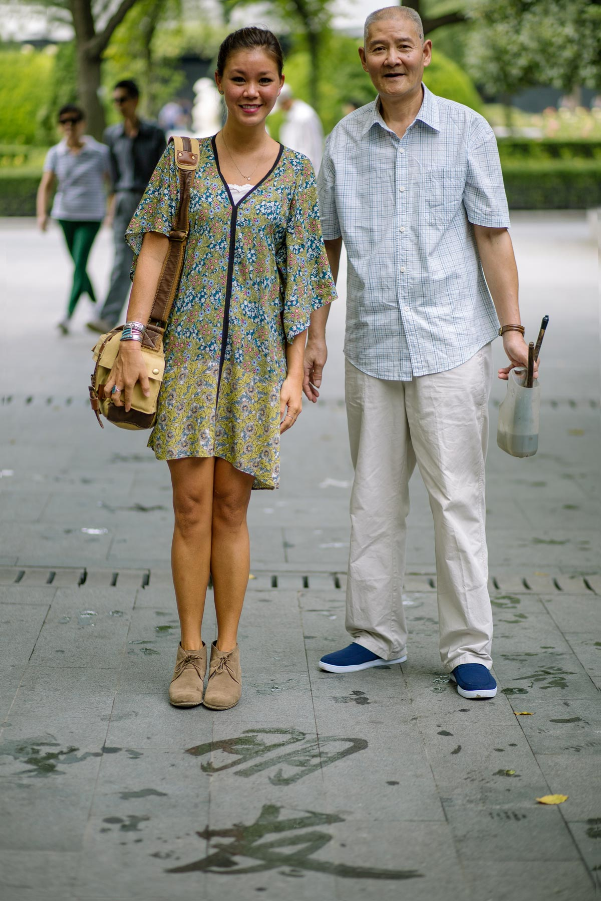 A man and woman smiling for the camera standing on the street