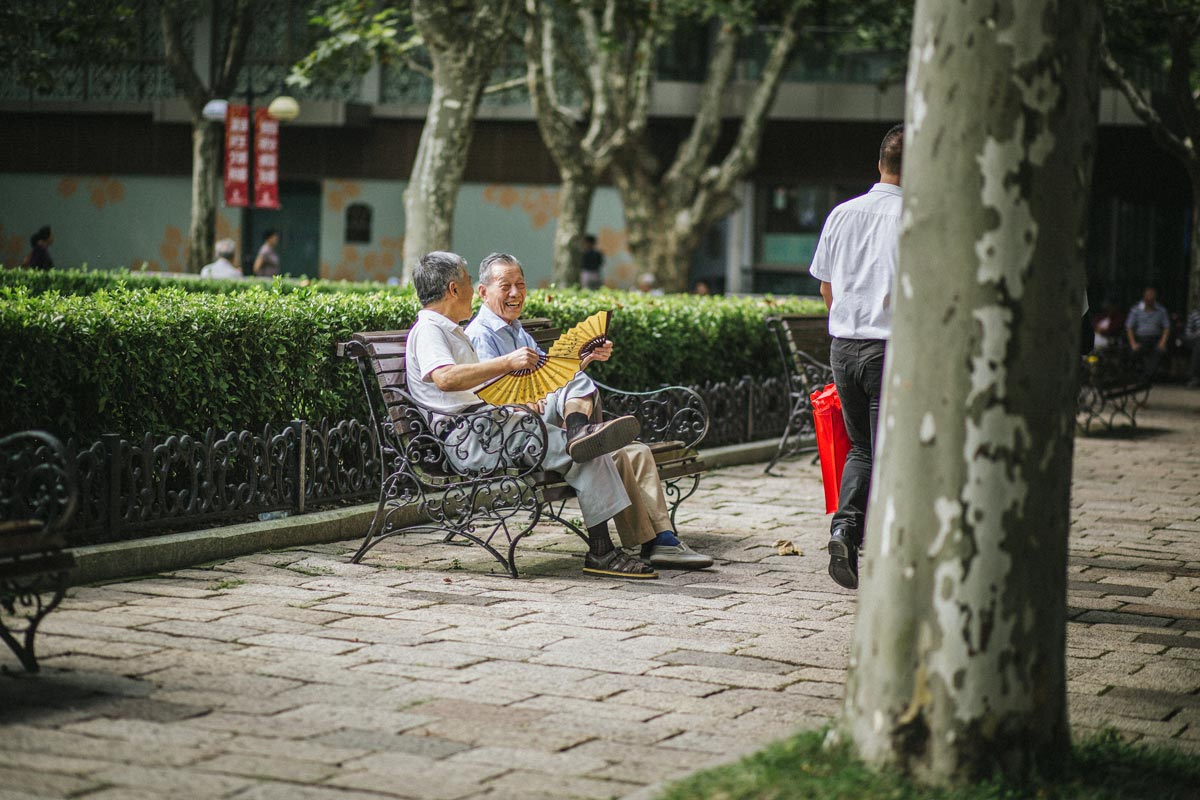 Two older gentleman sitting at a public bench chatting