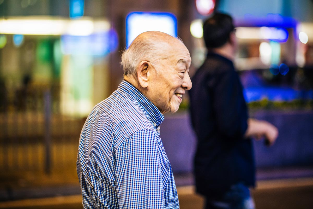 Night time shot of an older gentleman looking into the distance smiling