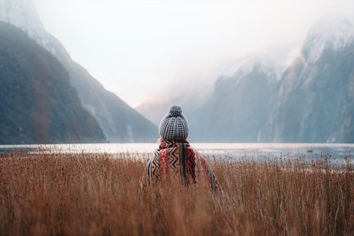 Woman standing in tall grass looking into wintery valley