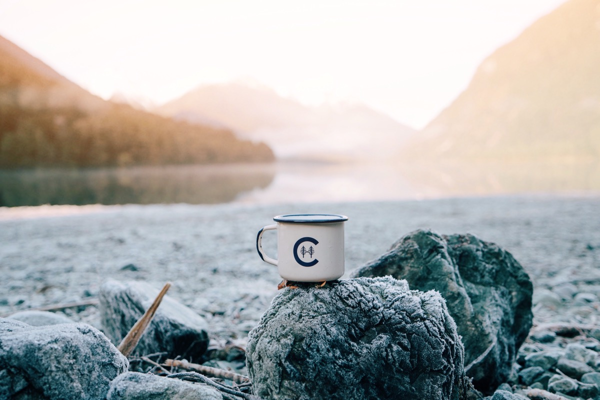 Coffee mug sitting on a rock at a camp fire