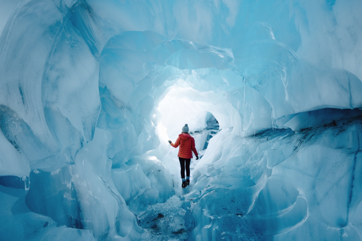 Woman walking through icy cave