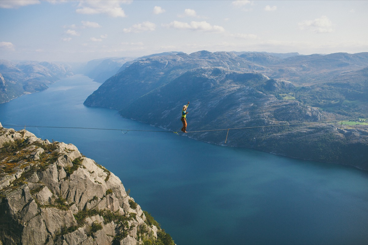 Person walking a thin rope across two cliffes
