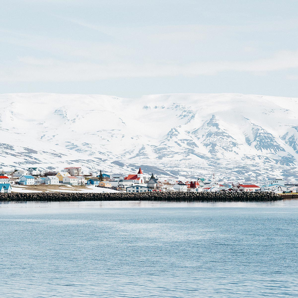 photo of coastal town set against snowy mountains