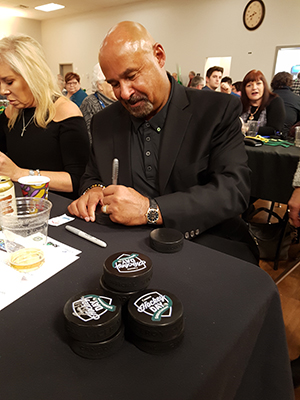 Five-time Stanley Cup champion Grant Fuhr signs autographs during the Hockey Day banquet