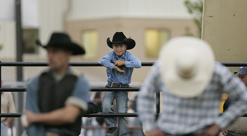 Zane Pozen, 8, of Elburn watches as the nights riders are announced before the beginning of the Championship Bull Riding competition during the Kane County Fair in St. Charles on Friday night. Kevin Sherman/ksherman@dailyherald.com/©Daily Herald