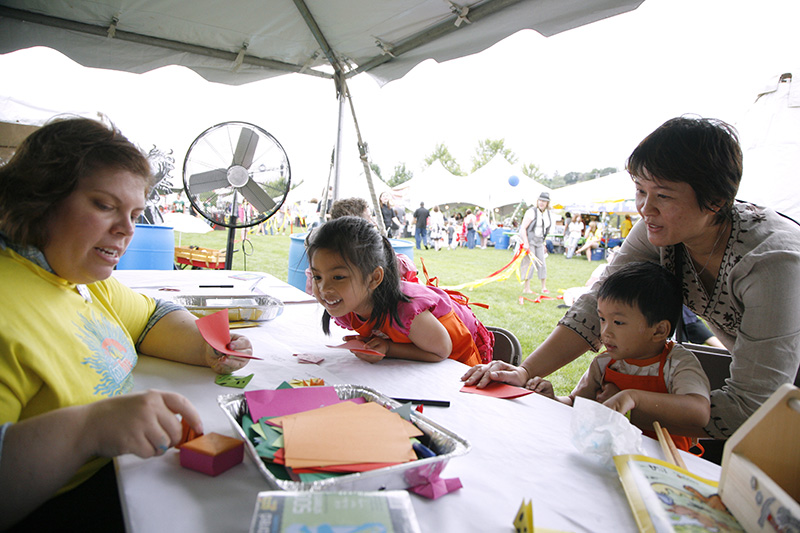 Ann Calverley, an art teacher from Coleman Elementary, shows Elgin residents Charlisa Mao, from the left, 4, Charlie Mao, 3, and their mom Pilai Mao how to make an origami fox during Elgins FoxFireFest in Festival Park on Saturday afternoon. Kevin Sherman/ksherman@dailyherald.com/©Daily Herald