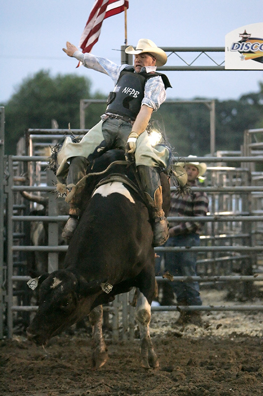 Rider Jim Kreke tries to stay on his bull, Milkman, during the bull riding competition at the McHenry County Fair in Woodstock on Friday evening. Kevin Sherman/ksherman@dailyherald.com/©Daily Herald
