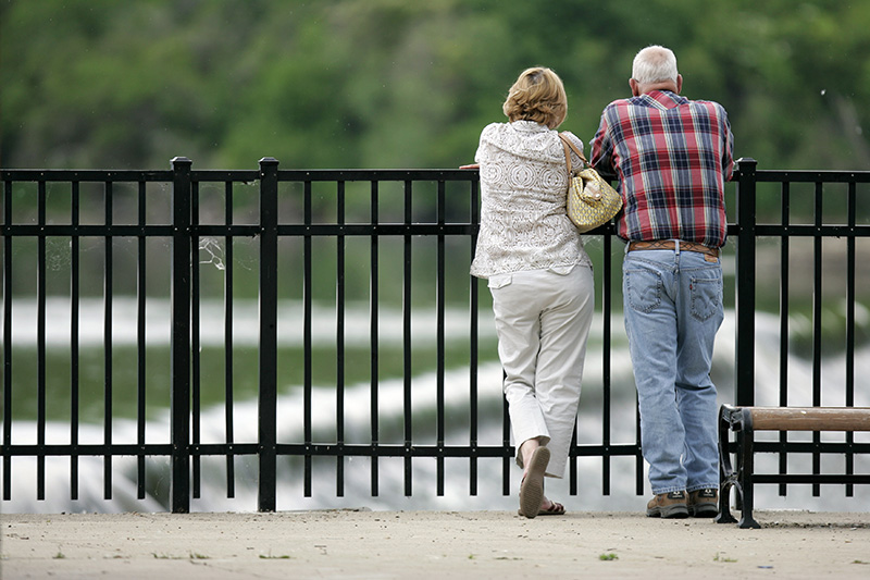 Huntley residents Mary and Carl Sickinjer cq look out over the Fox River at the Carpenter Dam historical site in Carpentersville. The couple were watching the fish attempting to scale the dam to swim up-river. KEVIN SHERMAN/ksherman@dailyherald.com/©Daily Herald