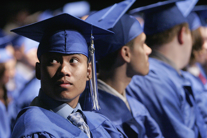 Maine West graduate Geomil Pasia  watches fellow students line up to receive their diplomas during graduation ceremonies at Rosemont Theatre on Sunday evening. Kevin Sherman/ksherman@dailyherald.com/©Daily Herald