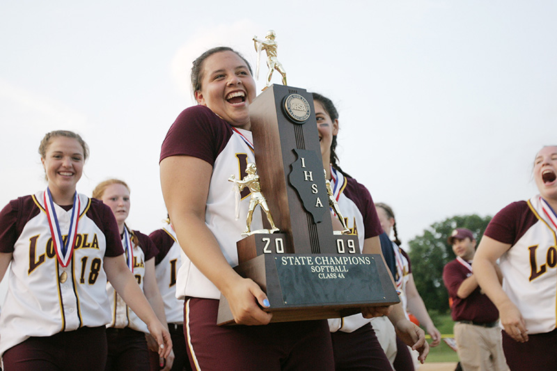 Loyola Ramblers pitcher Devin Miller shrugs as she carries the teams Class 4A state championship trophy after their 2-0 victory over Edwardsville at the EastSide Centre fields in East Peoria. Kevin Sherman/ksherman@dailyherald.com/©Daily Herald