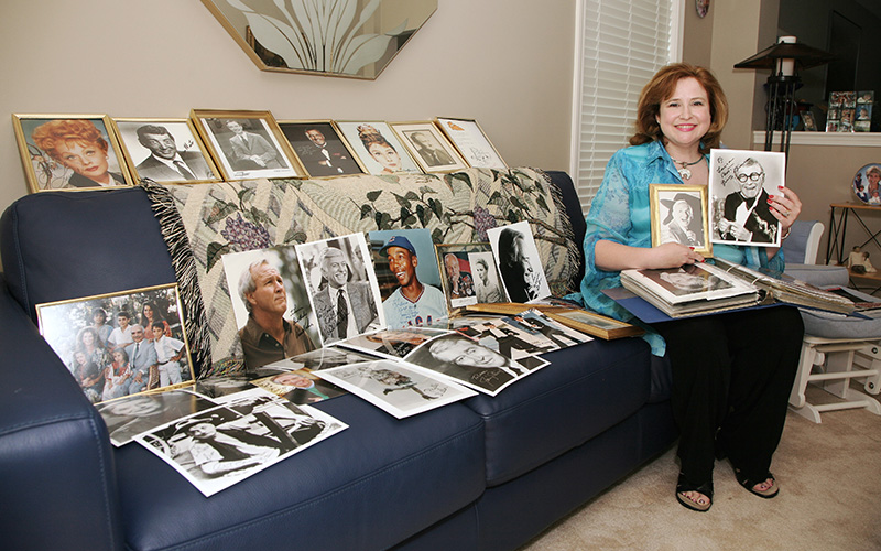 Laura Guzman poses with some favorite autographs from her collection at her home in Algonquin. Laura collected her first autograph when she was 13 and now has over 300 in her collection. Kevin Sherman/ksherman@dailyherald.com/©Daily Herald