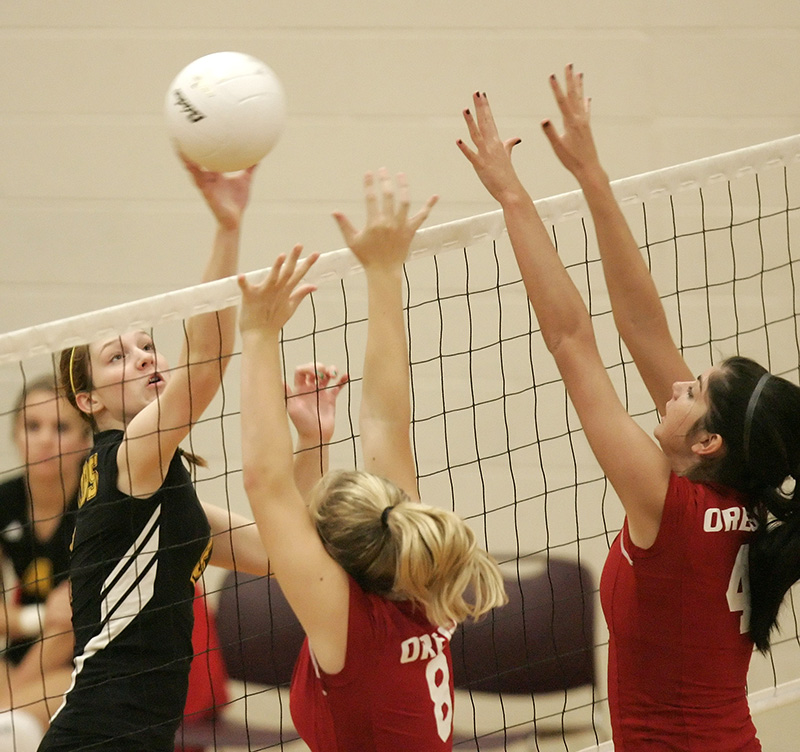 Jacobs Alyssa Ehrhardt (2) lifts a ball over Oregons Randi Wilkin (8) and Courtney Fane (4) during their game at the Huntley High School Varsity Volleyball Invite on Saturday morning.