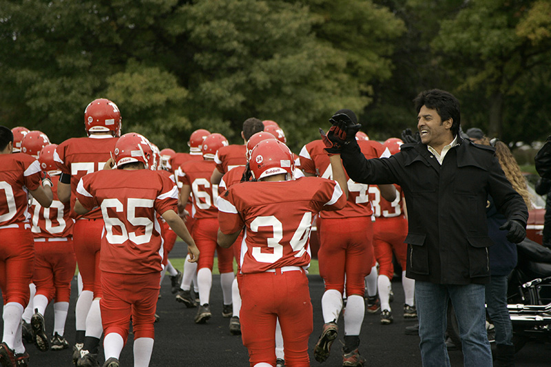 Actor Erik Estrada gives a high-five to players from Moosehearts football team before their Homecoming game on Saturday afternoon. Estrada was on hand to receive a donation from Moose International on behalf of the Safe Surfin Foundation.