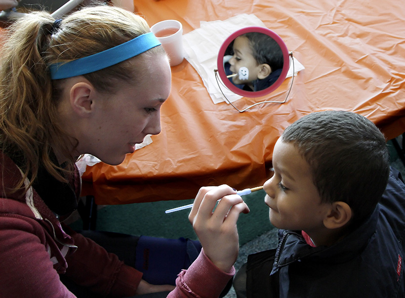 Kavari Chaney, 3, of Elgin gets a ghost painted on his cheek by Geneva resident Ellie Niezbar during the Halloween Family Fun Fair at The Centre of Elgin on Saturday afternoon.