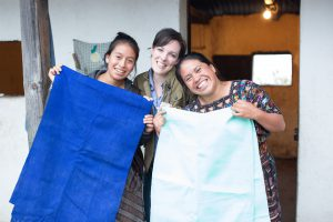 the-root-collective-founder-bethany-tran-posing-with-two-weavers-she-partners-with-through-a-local-weaving-cooperative-women-holding-fabric