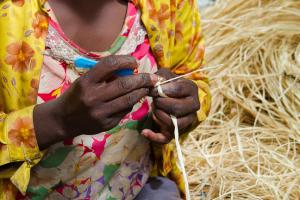 malagasy-woman-hand-stitching-raffia-handbag-raffia-hands-stitching-raffia-into-handbag