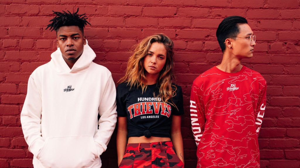 3 models in streetwear pose over brick wall