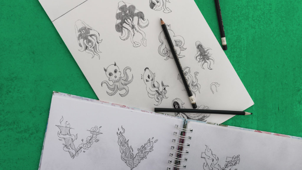 sketchbooks and pencils over green background