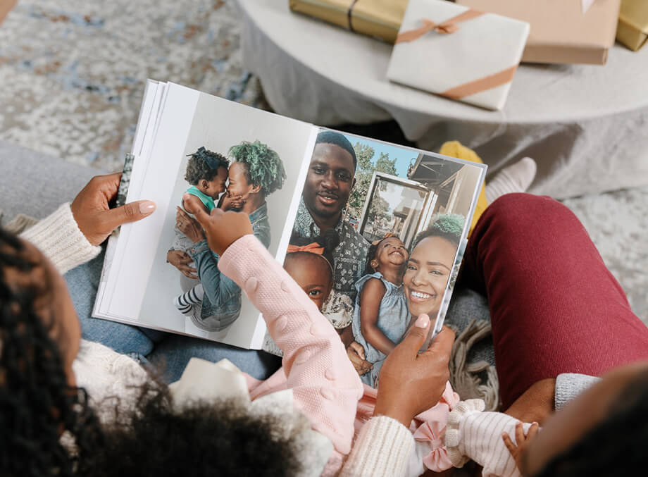Family on couch flipping through photo book