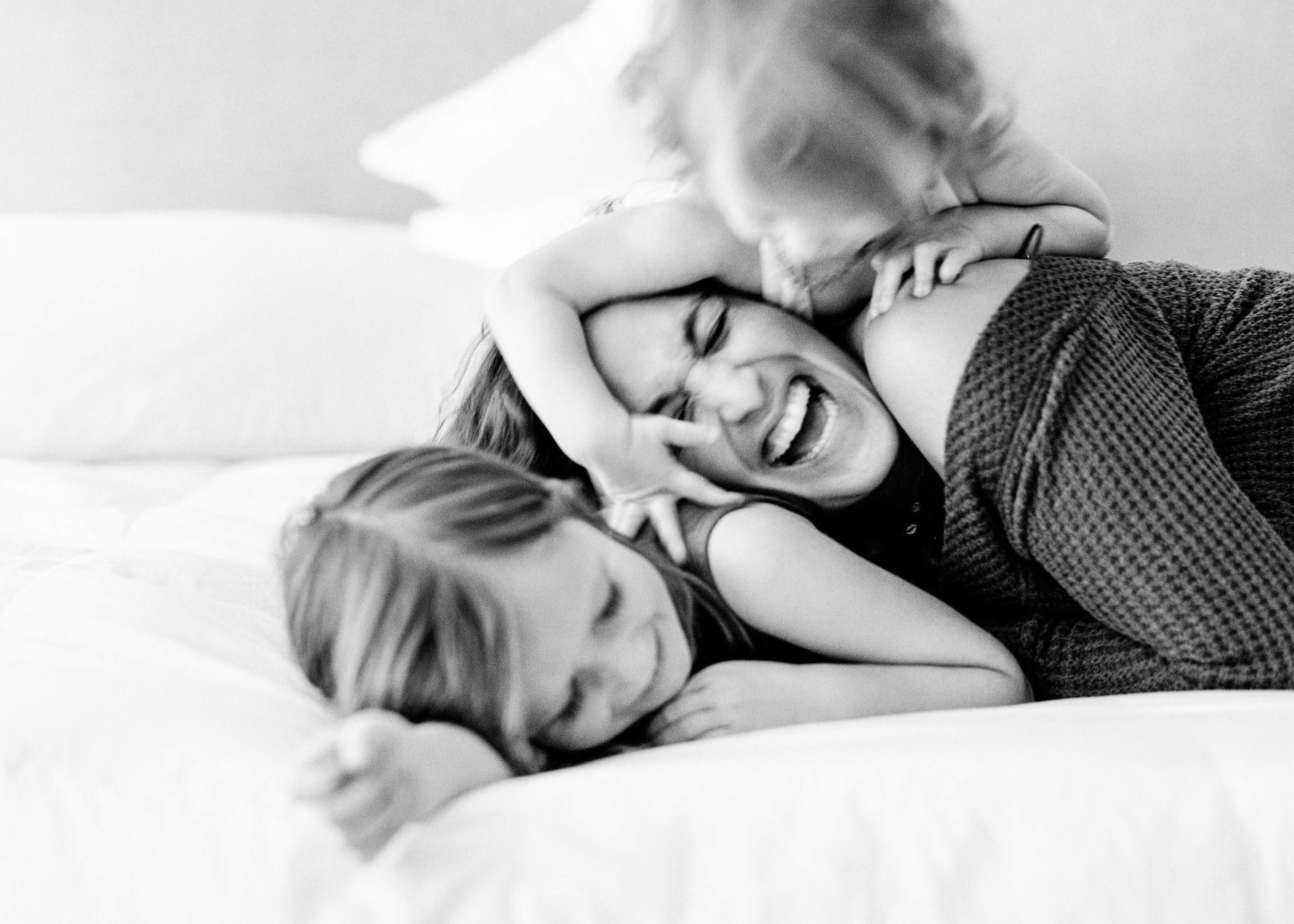 Little girl playfully jumping on top of mother and sister on bed