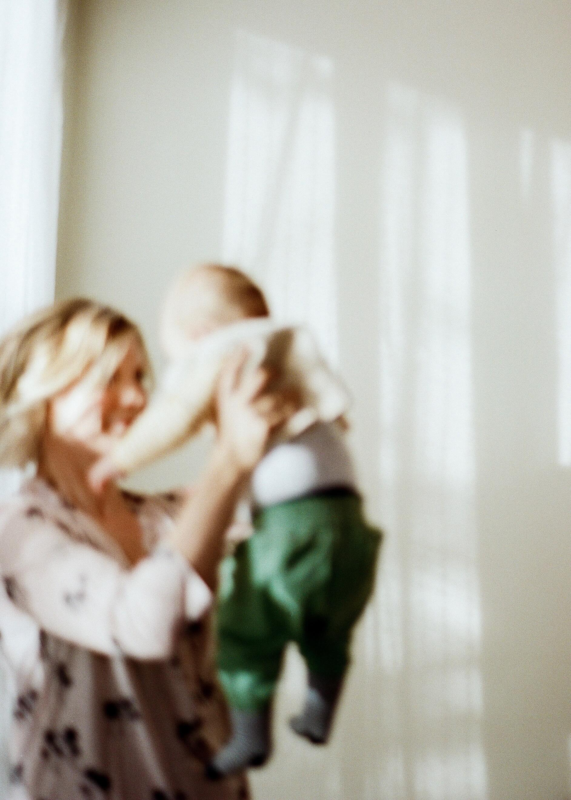 Blurred photo of mother holding up baby