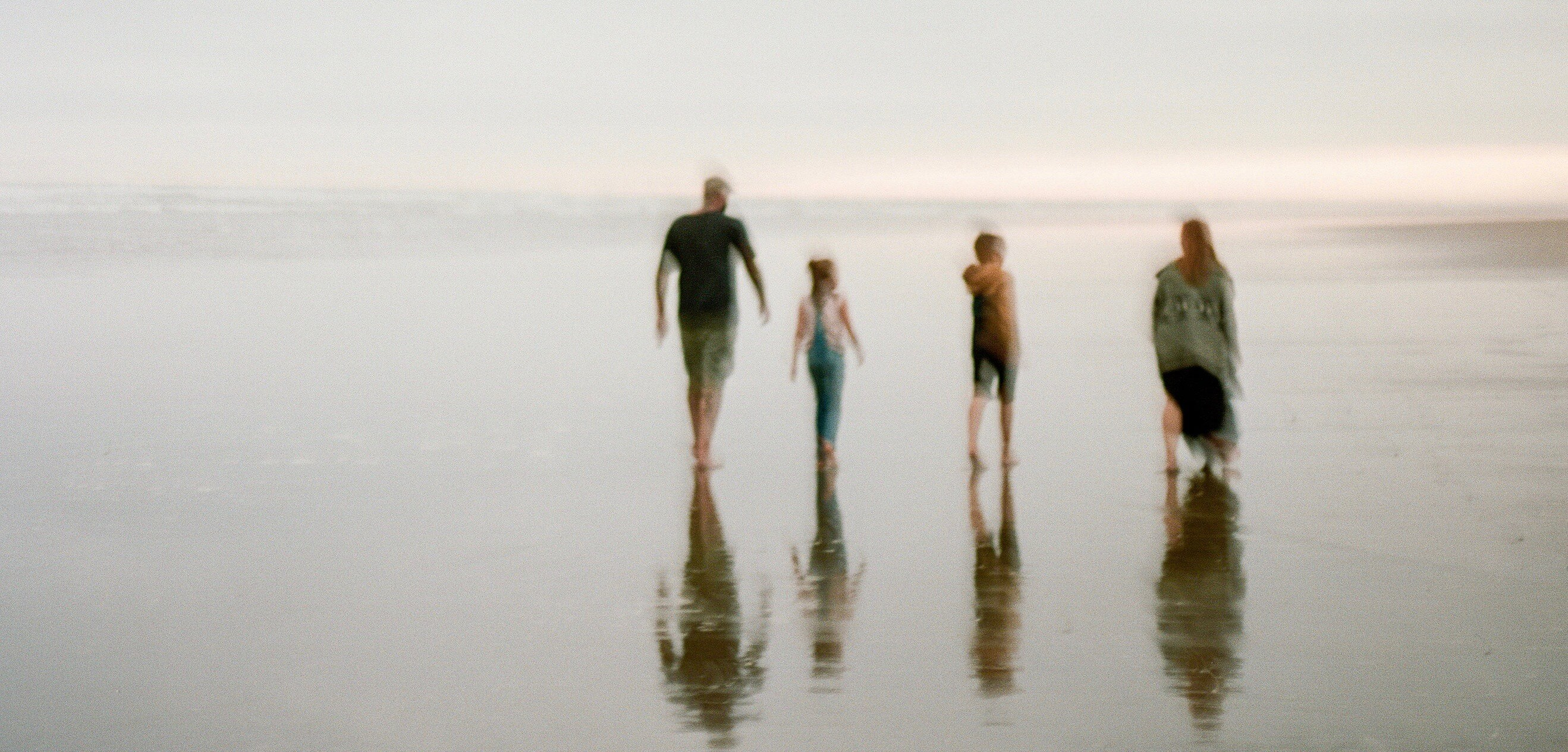 Blurred photo by Yan Palmer of family of four walking on beach