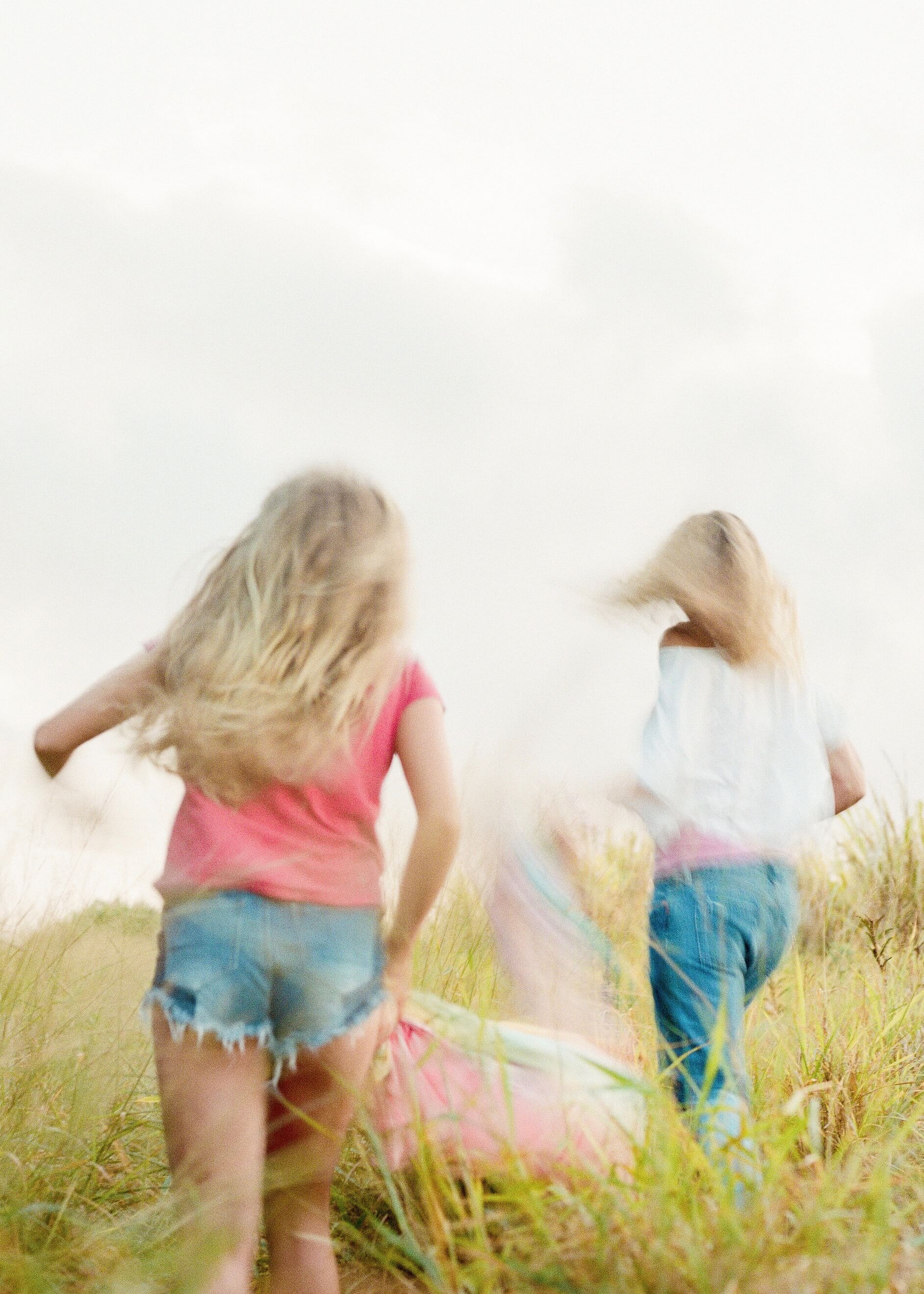 Blurred photo of little girls running in a field