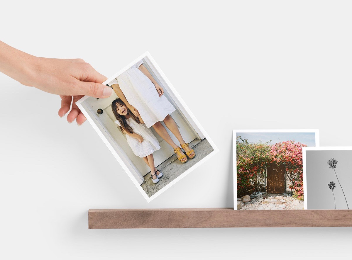 Hand placing photo print of little girl on Artifact Uprising Wooden Photo Ledge