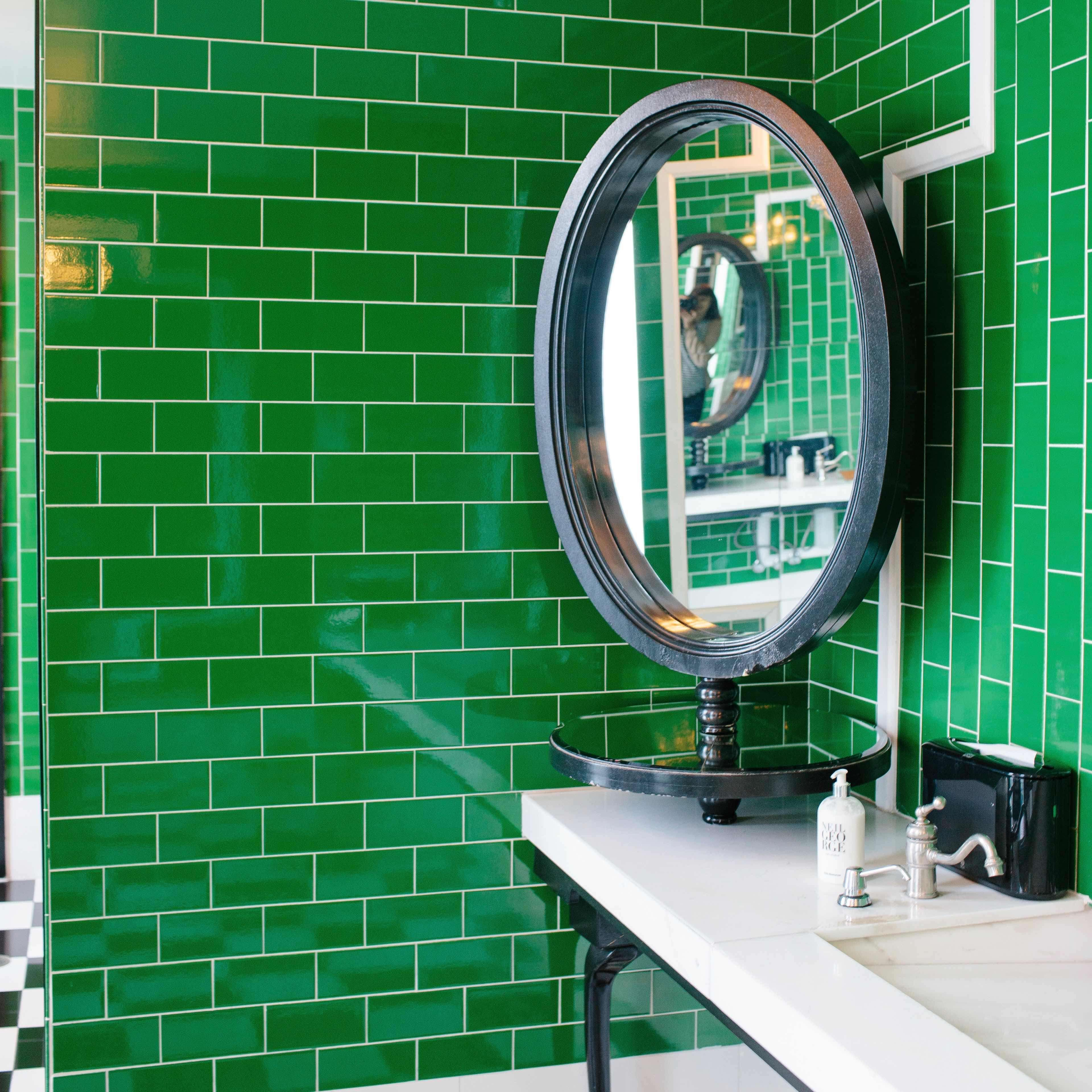 Green tile lines the walls of a washroom at the Viceroy