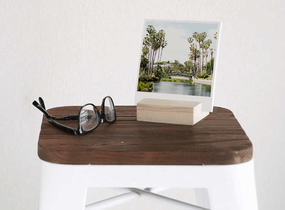 Photo prints held by wood block next to eyeglasses on stool