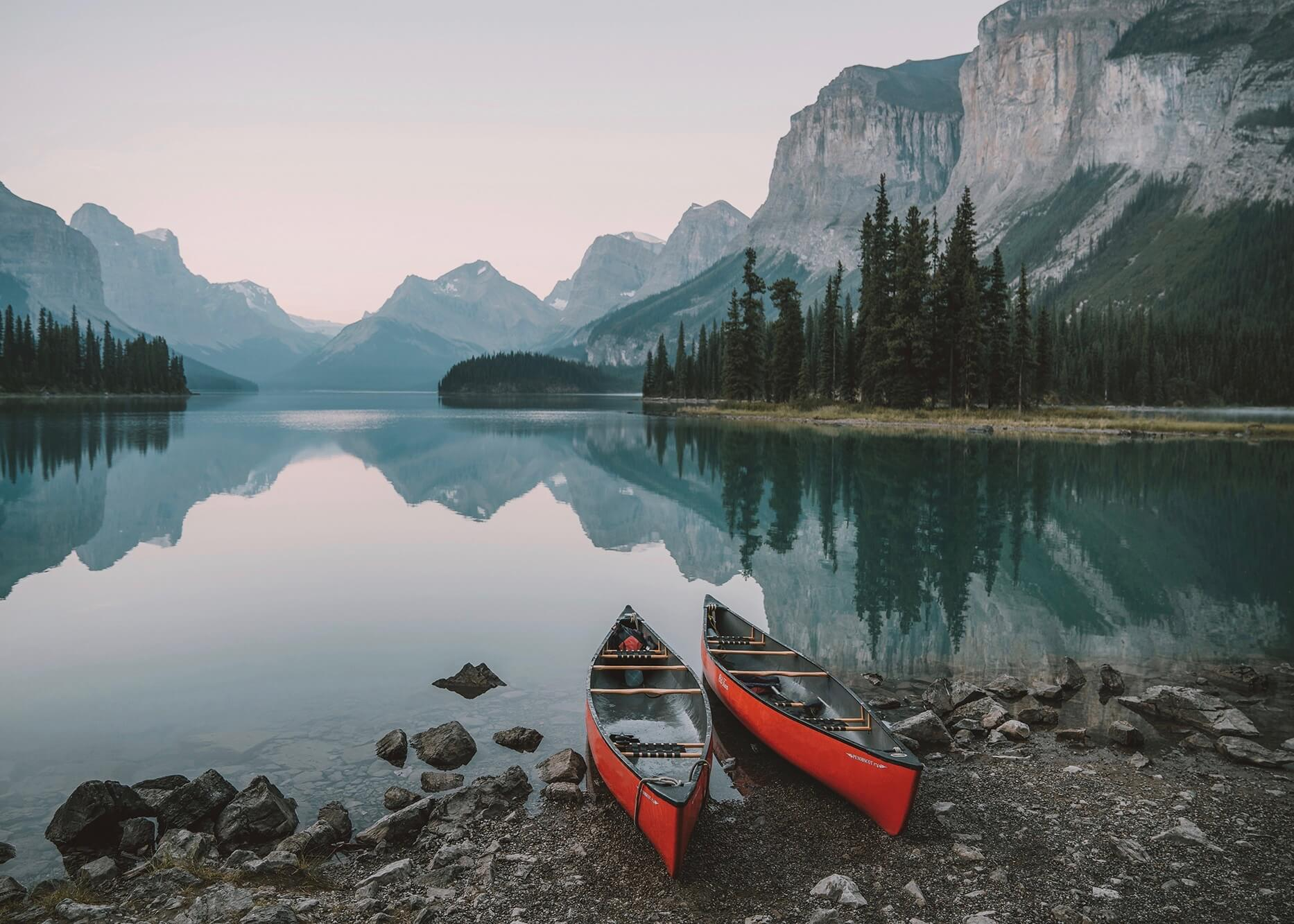 Emilie Ristevski photo of two empty canoes on the shore of an alpine lake