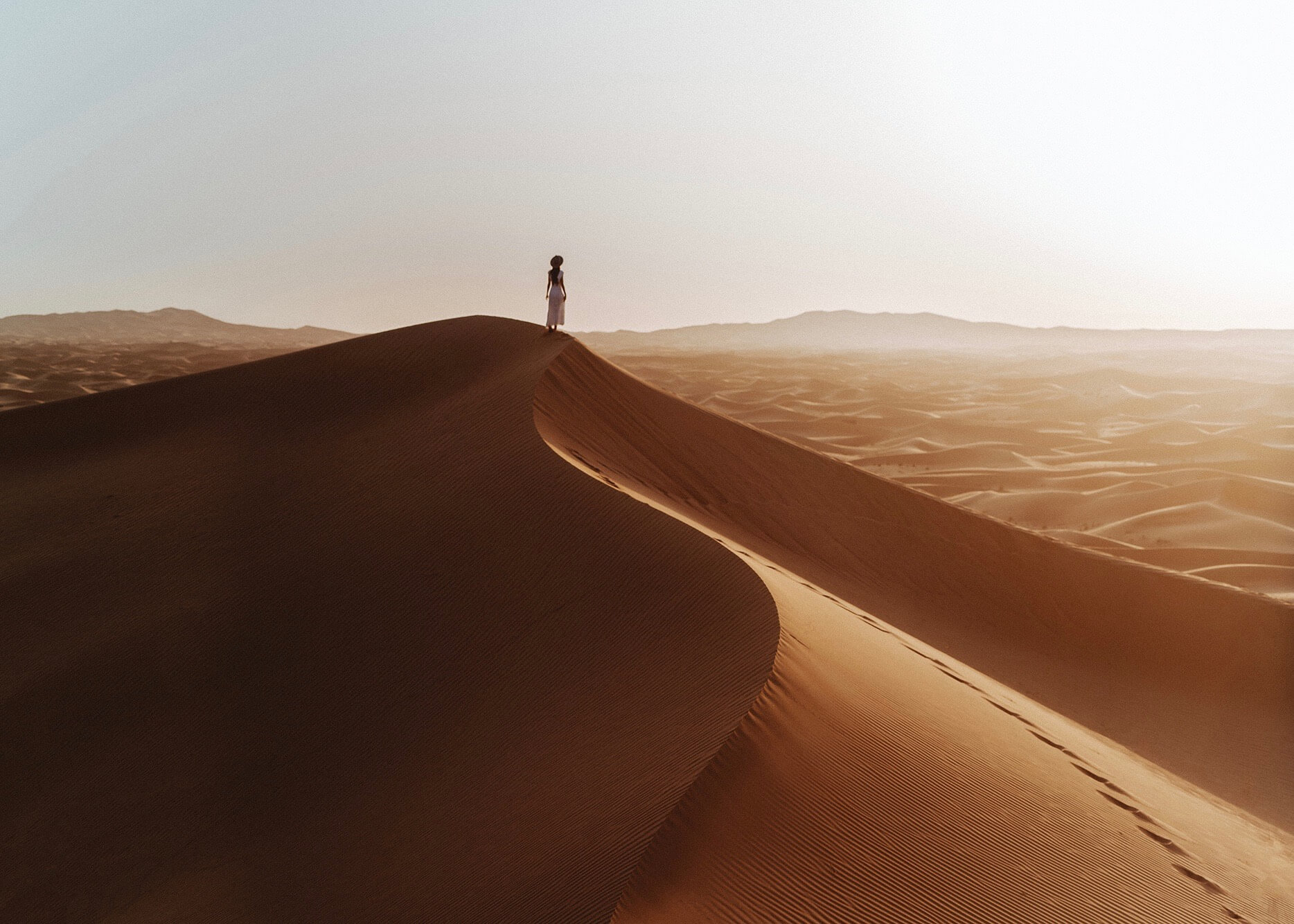 Emilie Ristevski photo of woman standing on top of sand dune facing away from the camera at golden hour