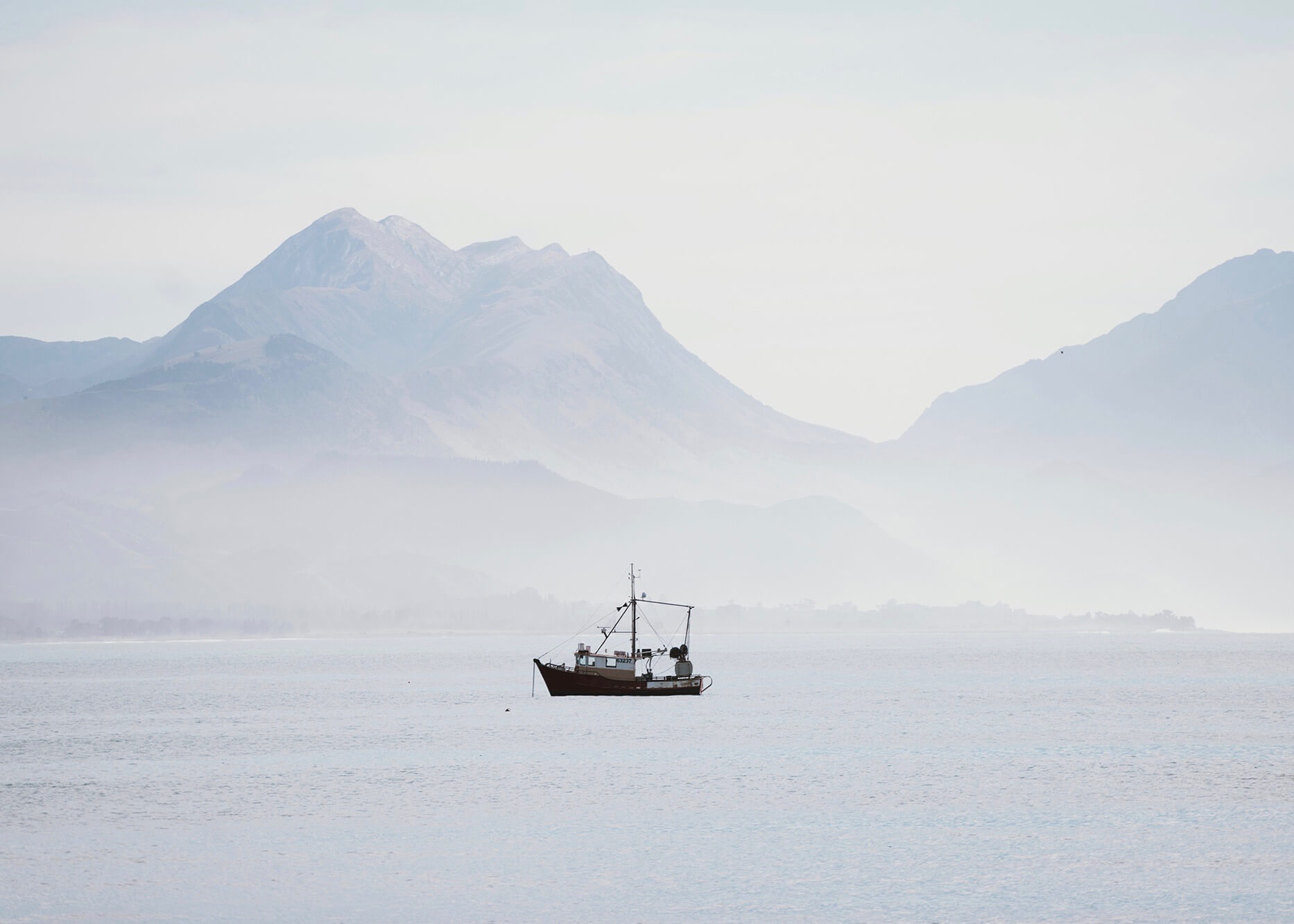 Photo of small boat in front of mountains and rolling fog