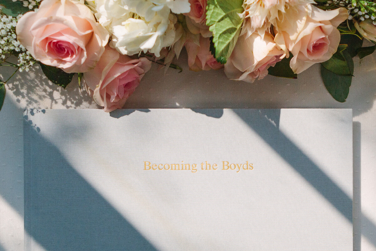 Cover of wedding guest book on table next to flowers