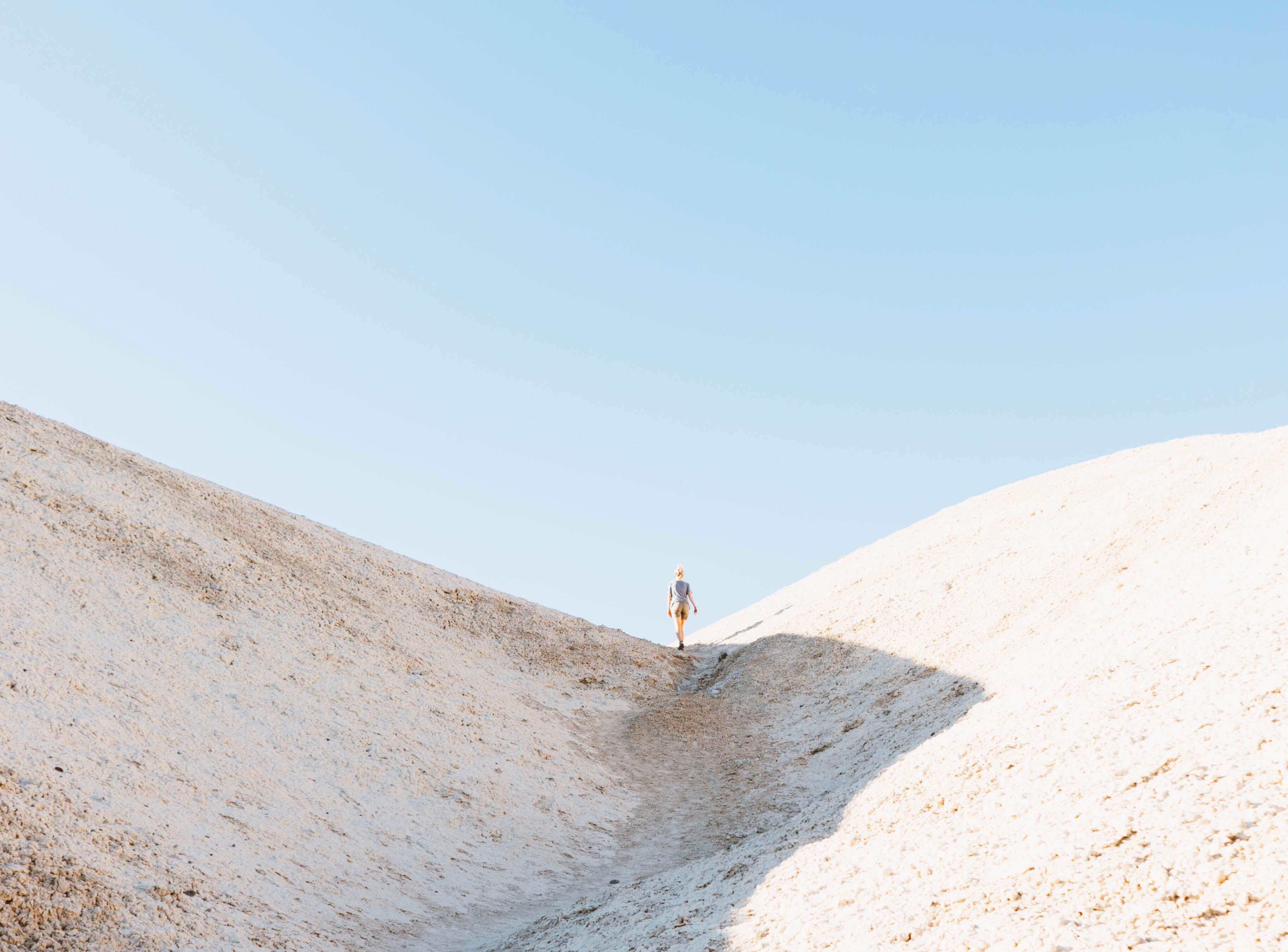 Someone climbing a hill in an arid landscape