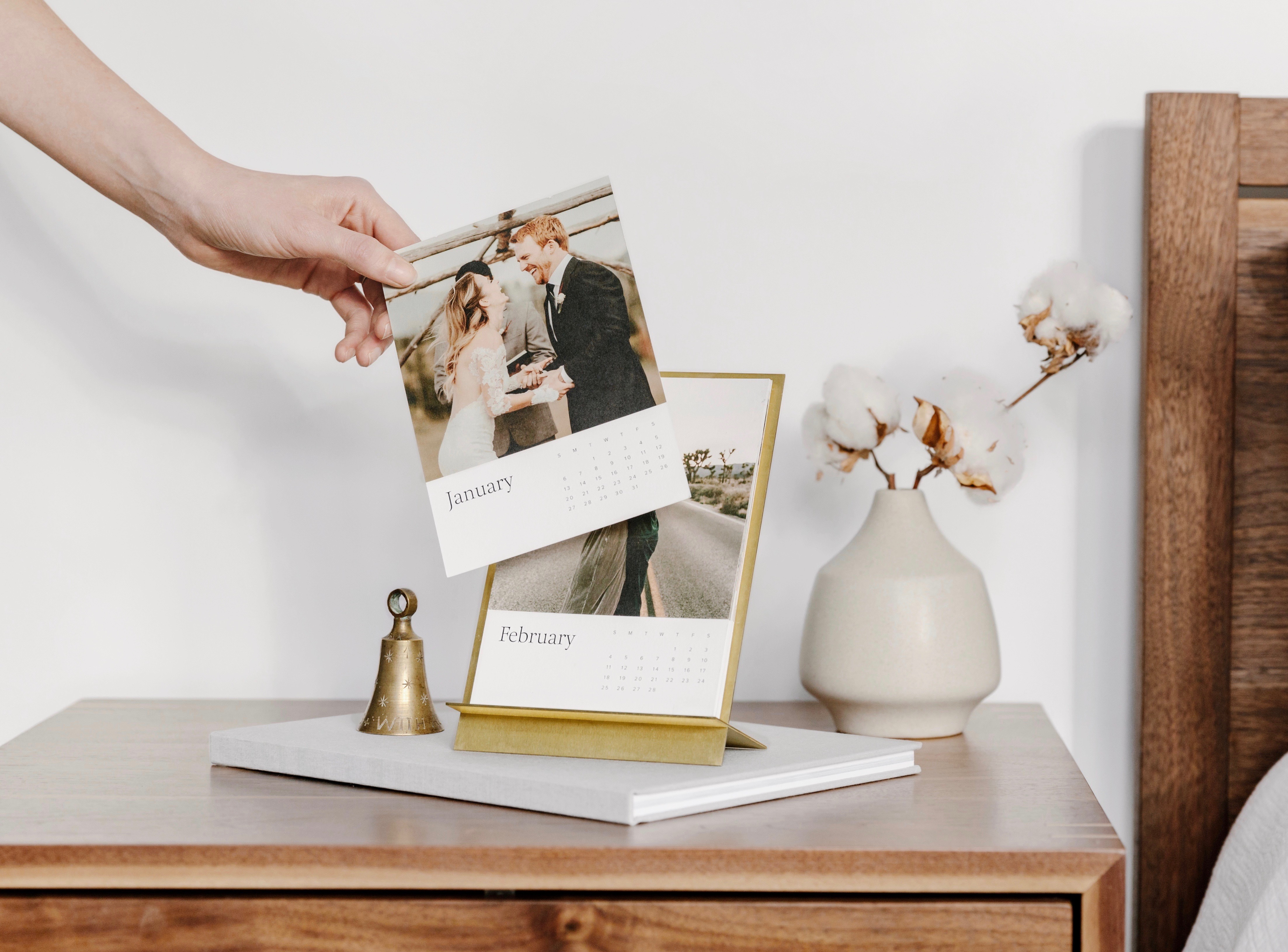 Hand changing month on brass easel calendar on nightstand