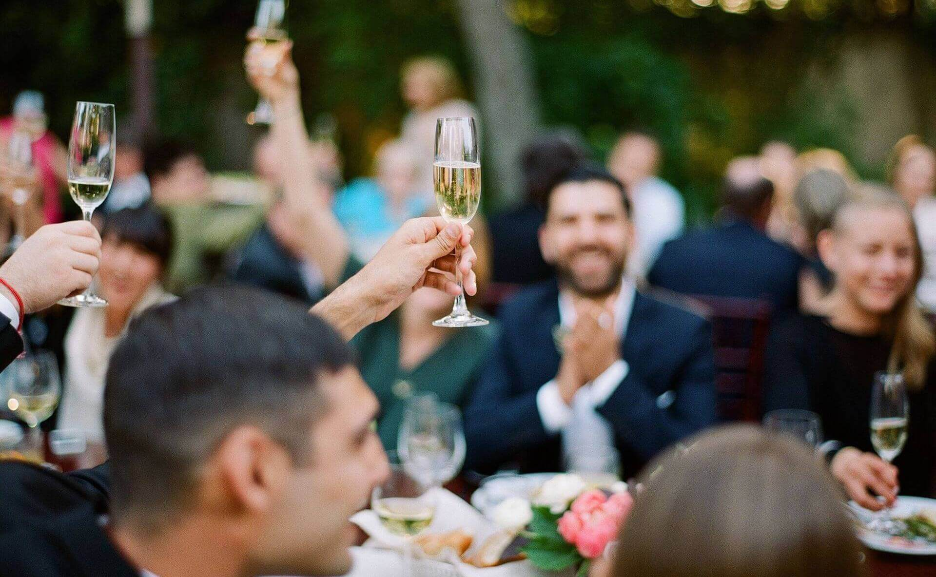 Hands holding up champagne for toast at wedding