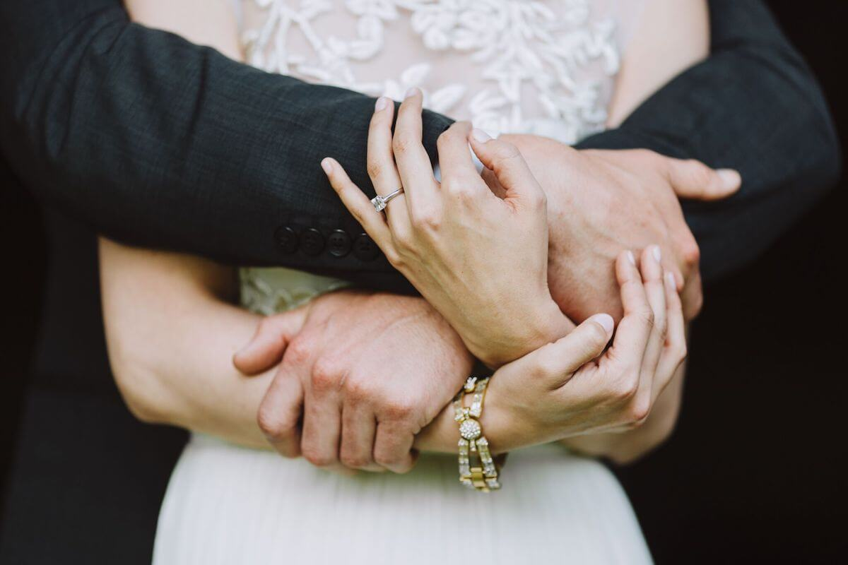 Close up image of bride and groom's hands around each other