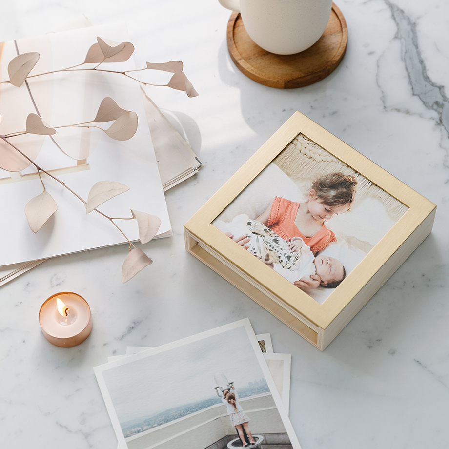 Brass and wood photo display box on marble countertop
