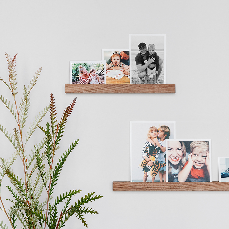 Photo prints of different sizes lined up on two offset wooden photo ledges