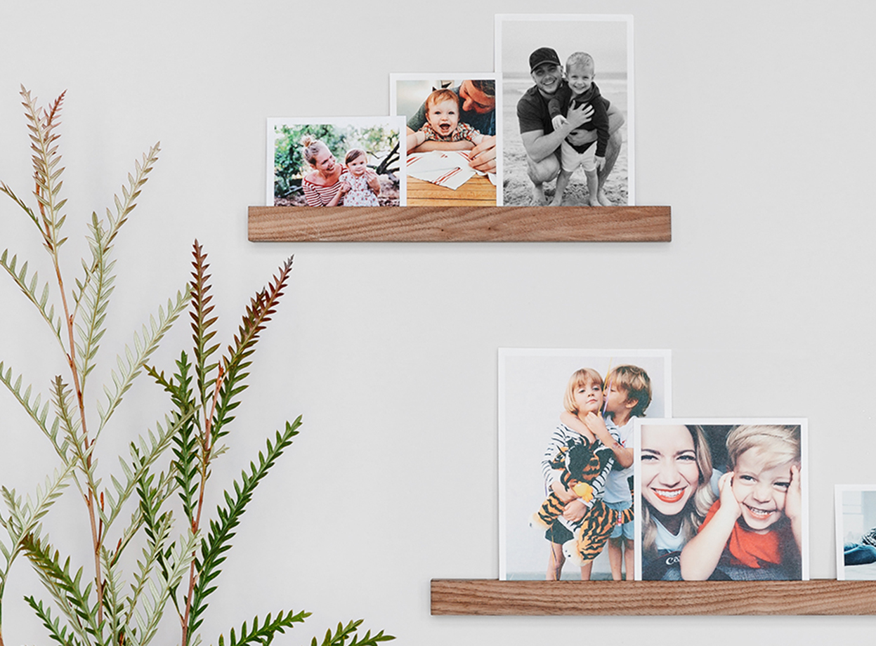 Different sizes of photo prints set on two wooden photo ledges